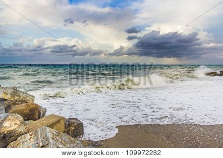 Rocky beach with sea view, waves of water and dark clouds on sky