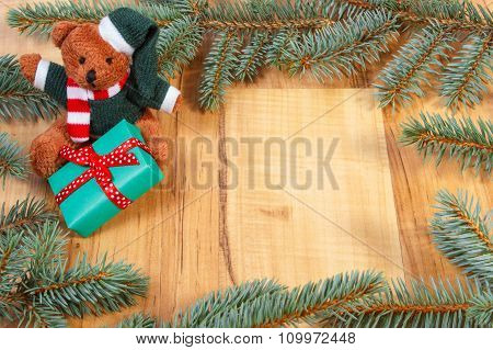 Teddy Bear With Green Gift For Christmas And Spruce Branches, Copy Space For Text