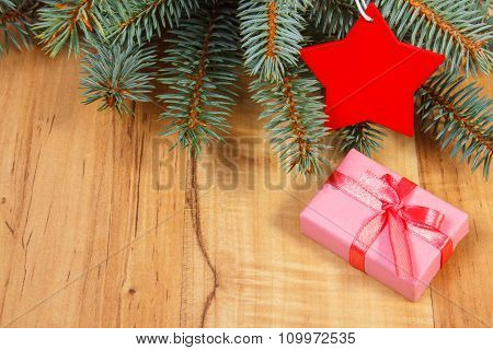 Spruce Branches With Red Wooden Star And Gift For Christmas
