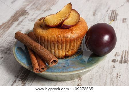 Fresh Baked Muffins With Plums And Cinnamon Sticks On Old Wooden Background, Delicious Dessert