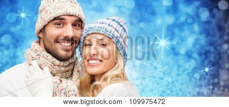 winter, fashion, couple, christmas and people concept - smiling man and woman in hats and scarf hugging over blue glitter or holidays lights background
