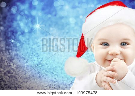 christmas, babyhood, childhood and people concept - happy baby in santa hat over blue glitter holidays lights background