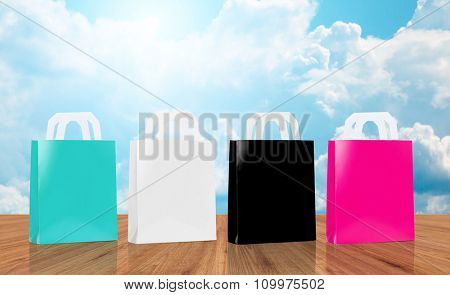 sale, consumerism and advertisement concept - many blank shopping bags blue, white, black and pink color over blue sky and clouds background