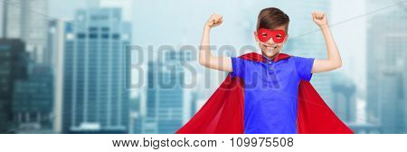carnival, childhood, power, gesture and people concept - happy boy in red super hero cape and mask showing fists over city buildings background