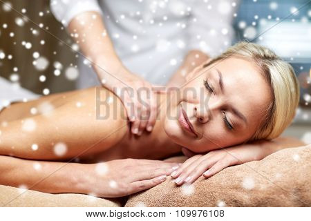 people, beauty, spa, winter and relaxation concept - close up of beautiful young woman lying with closed eyes and having hand back massage in spa salon with snow effect