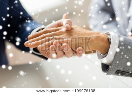 people, homosexuality, same-sex marriage and love concept - close up of happy male gay couple hands with wedding ring on over snow effect
