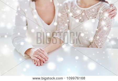 people, homosexuality, same-sex marriage and love concept - close up of happy married lesbian couple hugging over snow effect