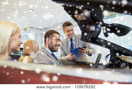 auto business, car sale, consumerism and people concept - happy couple with car dealer in auto show or salon over snow effect