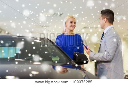 auto business, car sale, consumerism and people concept - happy woman with dealer talking in auto show or salon over snow effect