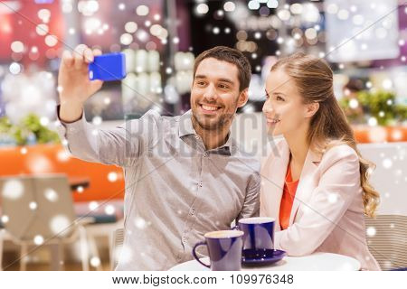 sale, shopping, consumerism, technology and people concept - happy young couple with smartphone taking selfie and drinking coffee or tea at cafe in mall with snow effect