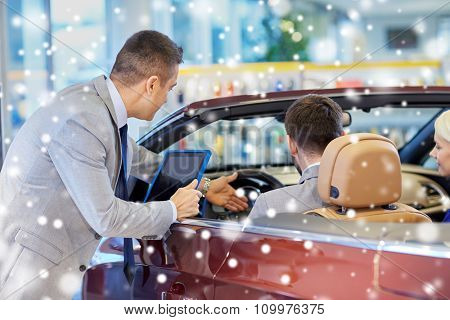 auto business, car sale, consumerism and people concept - happy couple sitting in cabrio car and dealer in auto show or salon over snow effect
