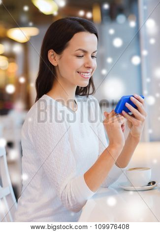 leisure, drinks, people, technology and lifestyle concept - smiling young woman with smartphone drinking coffee at cafe over snow effect