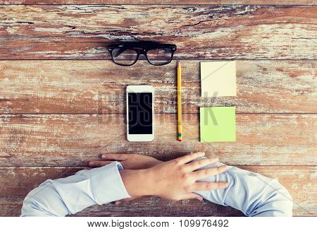 business, education and people concept - close up of female hands with smartphone, paper stickers, pencil and eyeglasses on table