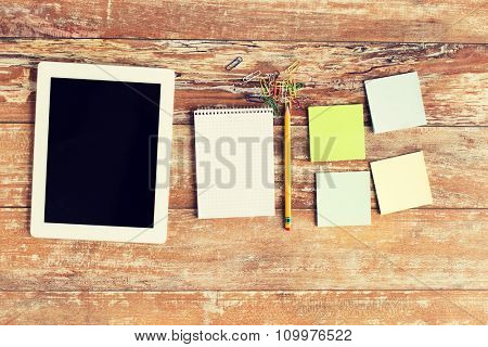 business, education, objects and technology concept - close up of notebook, tablet pc and stickers on table