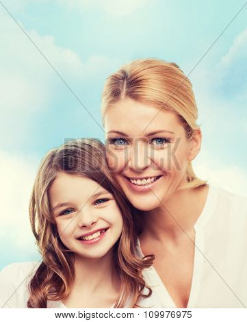 family, childhood, happiness and people - smiling mother and little girl over blue sky background