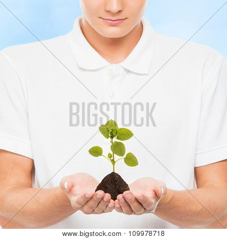 Young and handsome teenage boy holding soil with a plant on blue background. Ecology concept.