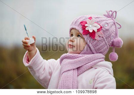 A Littlegirl  Blows Bubbles In Autumn