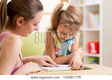 Mother teaching child daughter to read