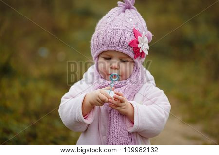 A Cute Little Baby Blows Bubbles In Autumn