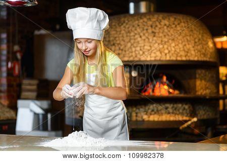 Funny happy chef girl cooking at restaurant kitchen and knead the dough