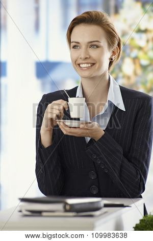 Happy young businesswoman drinking coffee, smiling, looking away.