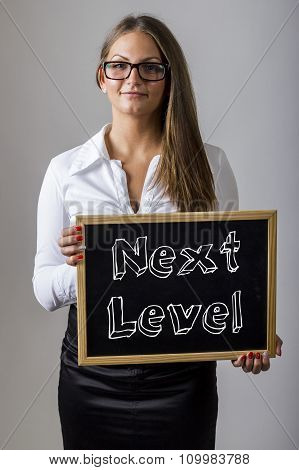 Next Level - Young Businesswoman Holding Chalkboard With Text