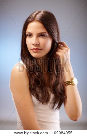 portrait of young brunette with hand in hair, looking away.