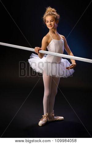 Smiling young ballet student practicing by ballet bar over black background.
