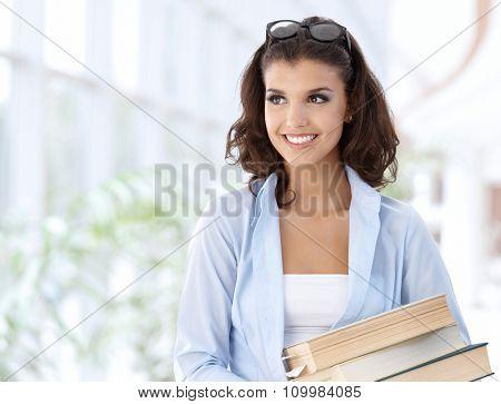 Happy female student on school corridor looking away, smiling.