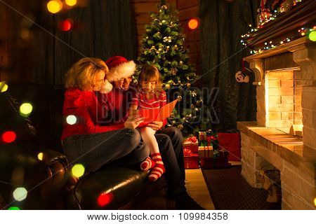 Happy family reading Christmas book sitting on sofa in front of fireplace in cozy living room in win