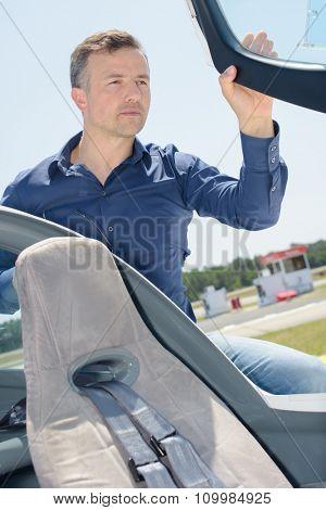 Man entering cockpit of aircraft