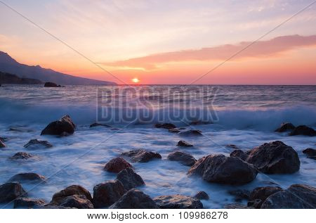 A Beautiful Sunrise Over The Sea, In The Foreground Large Stones