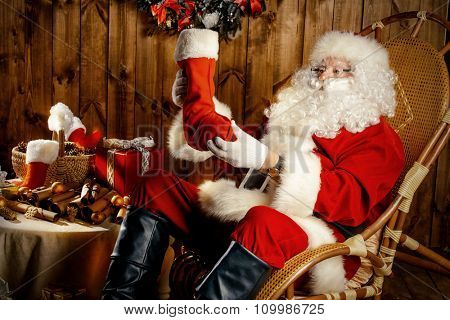 Good old Santa Claus with Christmas gifts at his wooden house. Sepia.