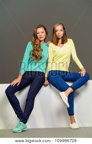 Two beautiful fashion models posing at studio in bright casual clothes. Beauty, fashion.