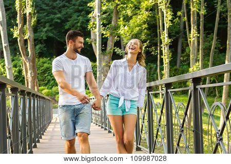 Guy and a girl walking on a bridge in the park.
