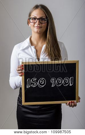 Iso 9001 - Young Businesswoman Holding Chalkboard With Text