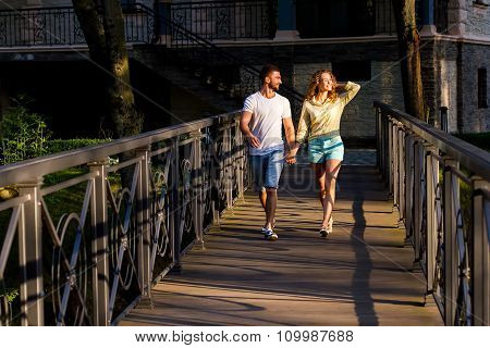 Lovers guy and girl walking on a bridge in the park.