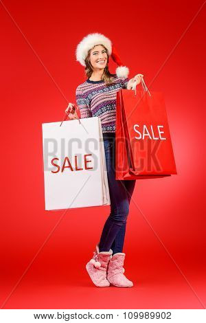 Full length portrait of a joyful young woman in Santa Claus cap holding shopping bags over red background. Christmas.