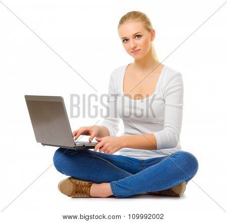 Young girl in jeans with laptop isolated
