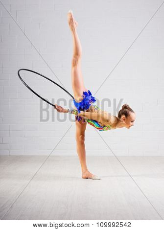 Young girl is engaged in art gymnastics on grey