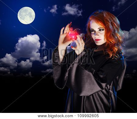 Young witch with potion on night sky background