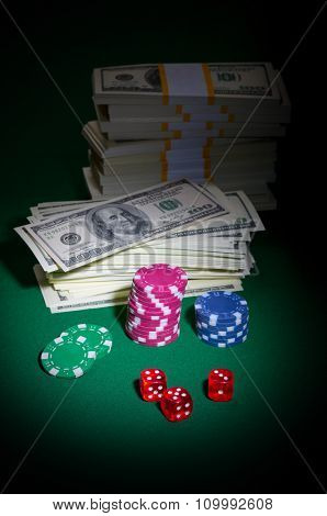 Dices chips and dollars on green table