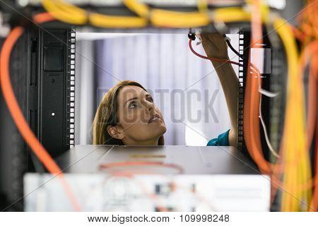 Technician looking at open server locker at the data centre