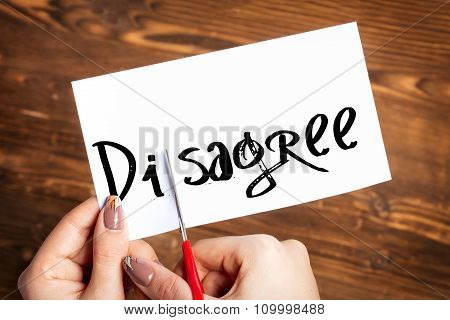Woman hands cutting card with the word disagree