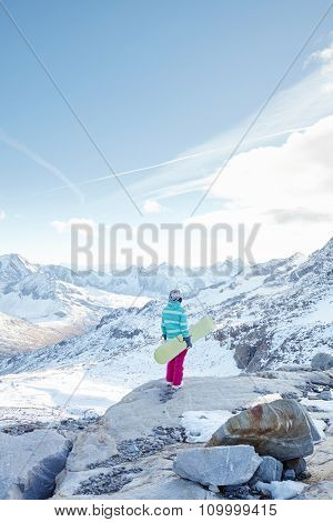 Back view of female snowboarder wearing colorful helmet, blue jacket, grey gloves and pink pants standing with snowboard in one hand and enjoying alpine mountain landscape - winter sports concept