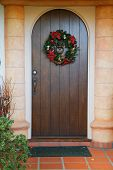 stock photo of christmas wreaths  - Vertical dark wood door with green and red Christmas wreath - JPG