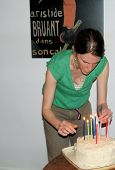Woman Placing Candles In Birthday Cake