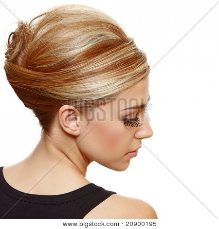 beautiful blond woman with false long eyelashes wearing hair in a classic french roll updo style.