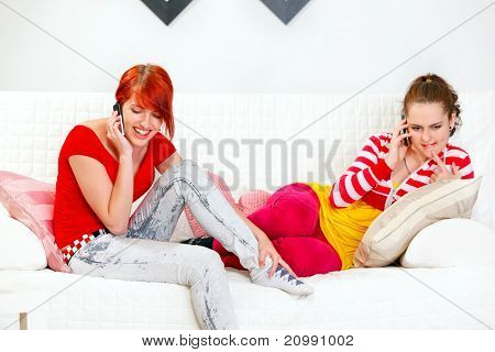 Young girlfriends sitting on sofa and talking on mobiles