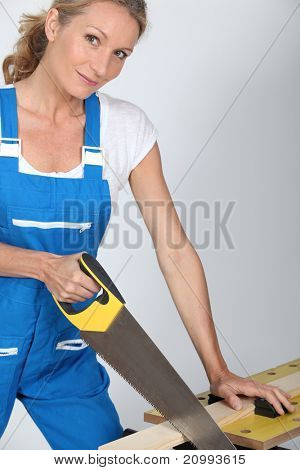 Woman sawing a piece of wood